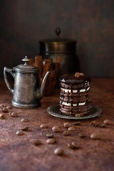 Chocoladecake en uitstekende koffiekan. chocoladedrops en koffiebonen