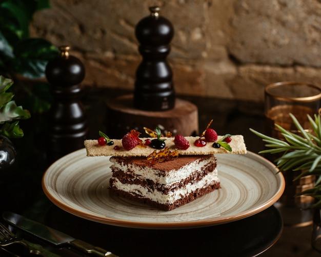 Chocoladecake gegarneerd met koekje en bessen
