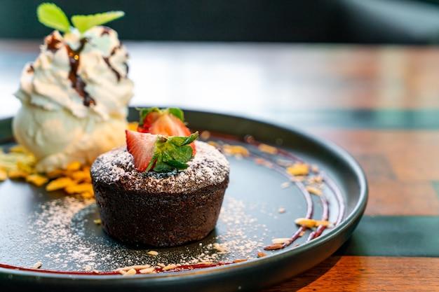 Chocoladecake lava met aardbei en vanille-ijs op zwarte plaat