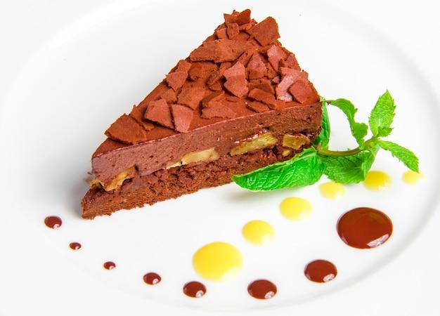 Chocoladecake met chocolade creame op wit wordt geïsoleerd dat