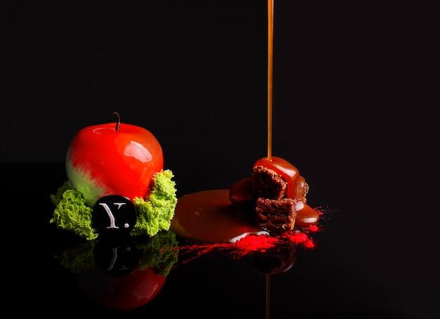 Chocoladecake met karamelmousse in het spiegelglazuur. met noten. op de zwarte achtergrond. reflectie.