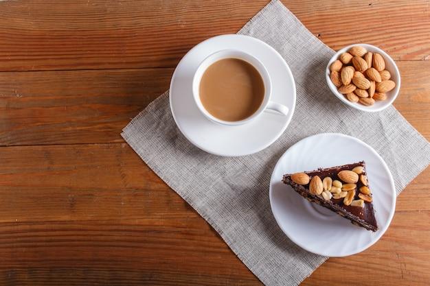 Chocoladecake met karamelpinda's en amandelen op een bruine houten achtergrond