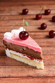 Chocoladecake met kersen op houten achtergrond.