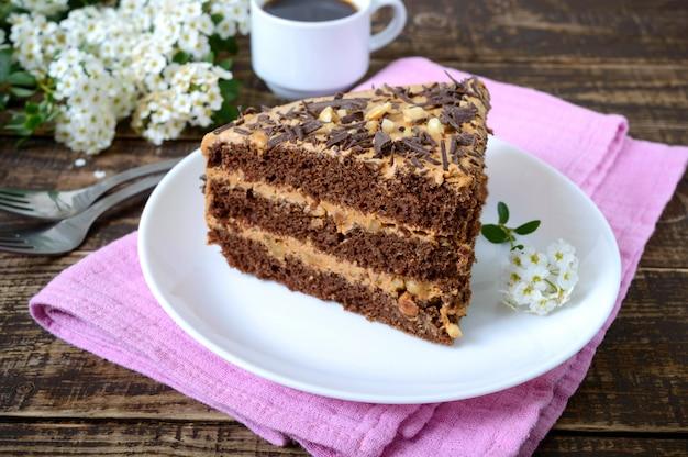 Chocoladecake met nootroom op een houten lijst. een fluitje van een cent op een bord en een kopje koffie.