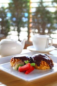 Chocoladecake met roomijs en aardbeien op een witte plaat