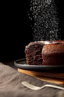 Chocoladecake met suikerpoeder wordt bestrooid op een zwarte plaat die