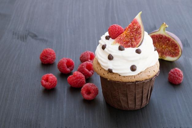 Chocoladecake met vijgen en frambozen op een zwarte achtergrond.