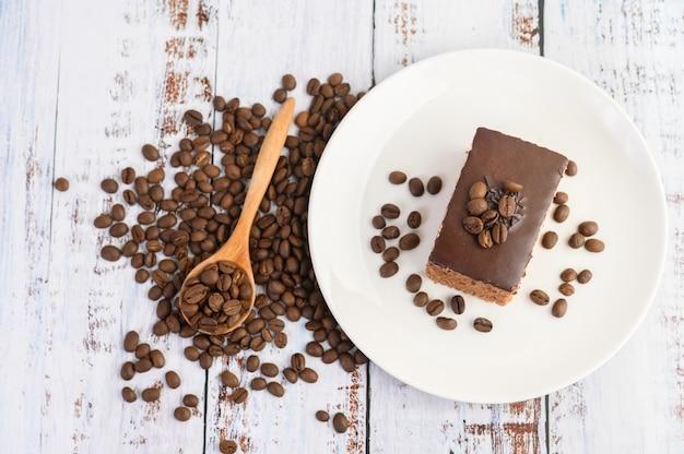 Chocoladecake op een witte plaat en koffiebonen op een houten lepel op een houten lijst.