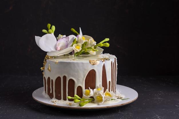 Chocoladecake versierd met bloemen en gegoten wit suikerglazuur