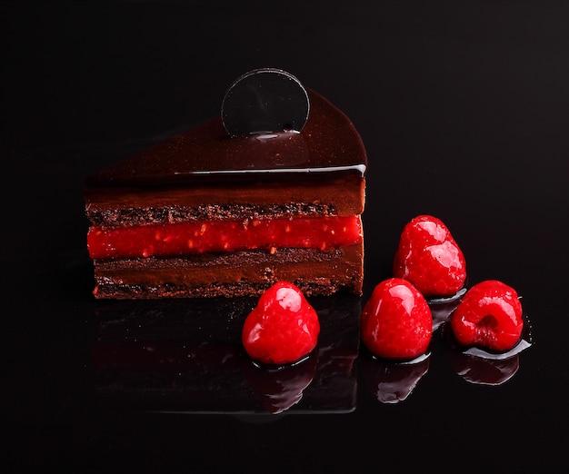 Chocoladecake zacher met framboos, mousse in de spiegelreflectie, sectie. op de zwarte achtergrond.
