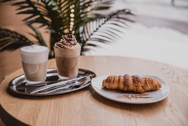 Chocoladecocktail met ijs. cappuccino en croissant in het café. koffie in de ochtend, ontbijt in een gezellig café bij het raam