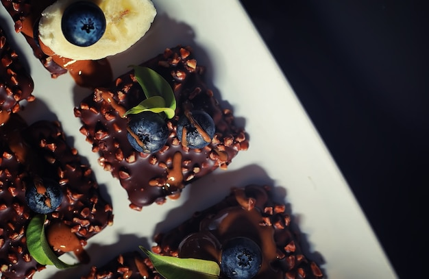 Chocoladedessert met noten en verse bessen. zoete snack voor koffiekoekje in glazuur en notenkruimels met fruit.