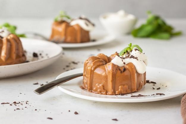Chocoladedessert versierd met slagroom, geraspte chocolade en munt. panna cotta.