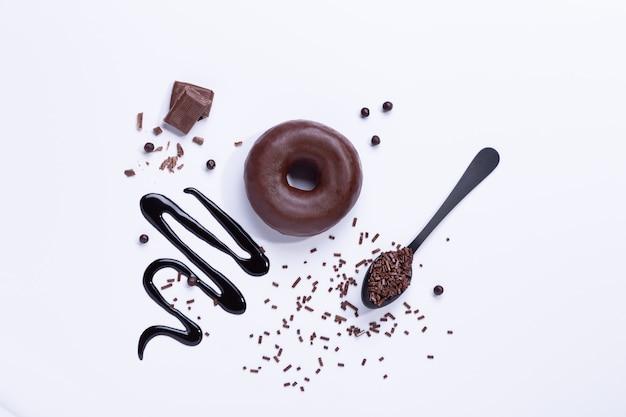 Chocoladedoughnut en chocolade op witte achtergrond. bovenaanzicht.
