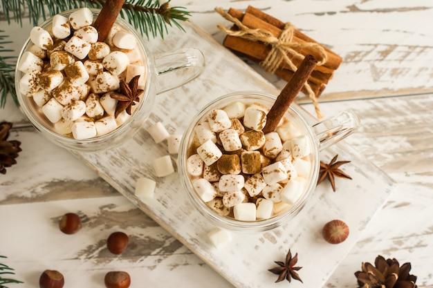 Chocoladedrank of cacao met marshmallow in glazen mokken op een witte houten tafel. bovenaanzicht van de drank kaneelstokjes, noten, anijssterren.