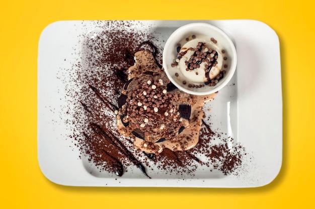 Chocoladefondant met vanille-ijs op een gele achtergrond