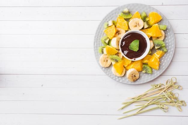 Chocoladefondue met fruit op witte lijst. concept zomerfeest. kopieer ruimte