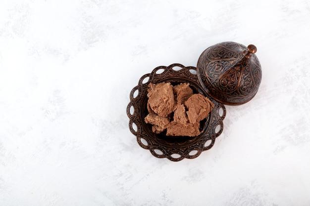 Chocoladehalva in bruine metalen kom turkse snoepjes bovenaanzicht kopieerruimte