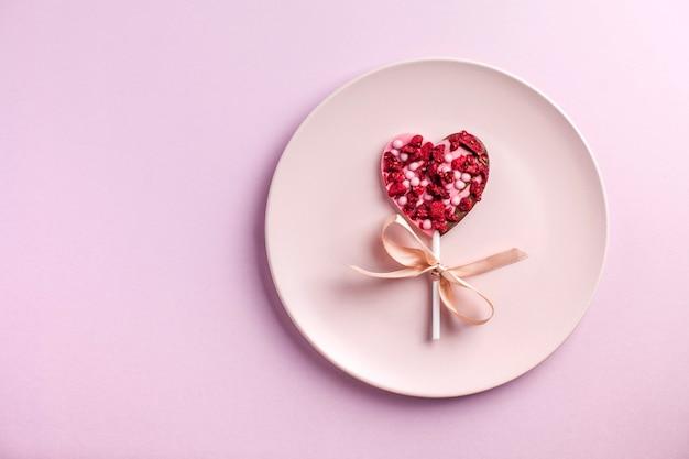 Chocoladehart op een roze bord op een roze achtergrond het concept van een romantisch diner valentijnsdag