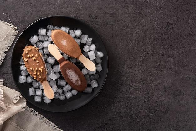 Chocoladeijslollys en verpletterd ijs op blauw bord