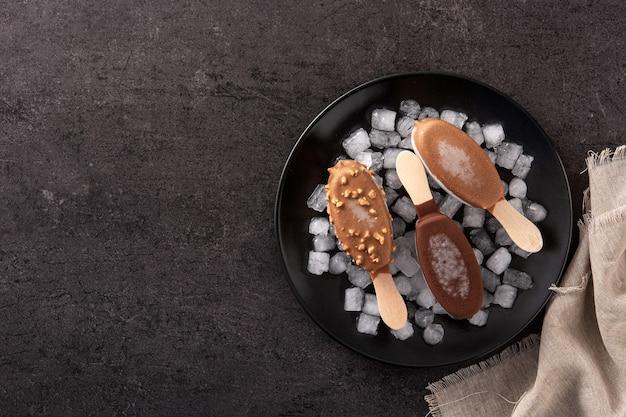Chocoladeijslollys en verpletterd ijs op zwarte lijst