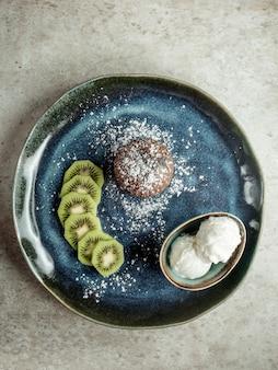 Chocoladekoekje met gesneden kiwi en roomijs