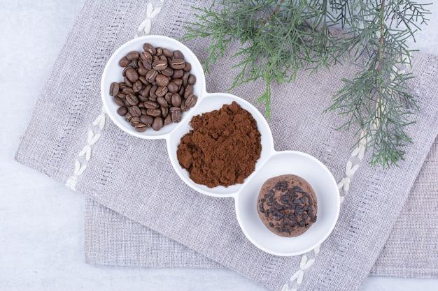 Chocoladekoekjes, cacao en koffiebonen in witte kommen.