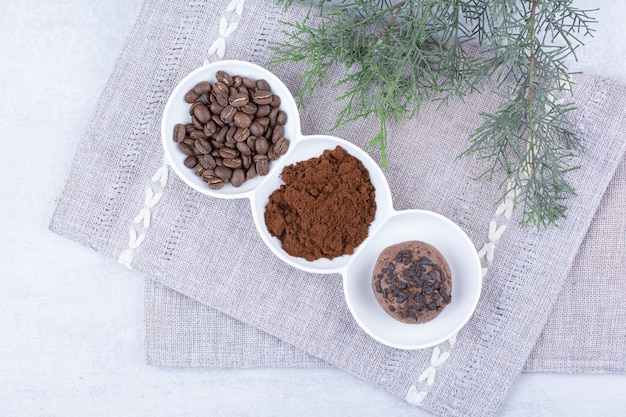 Chocoladekoekjes, cacao en koffiebonen in witte kommen