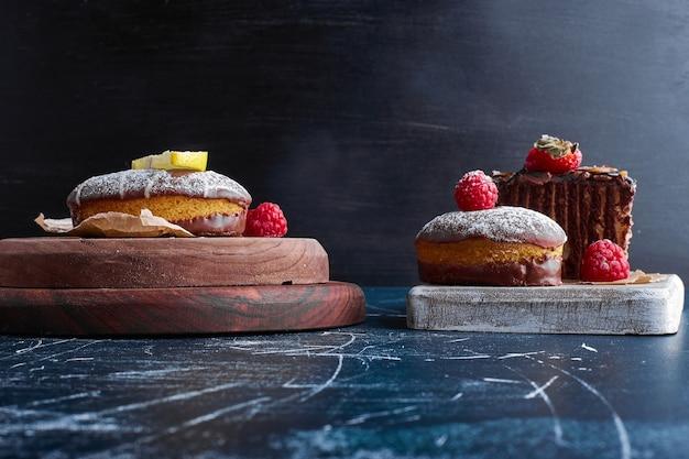 Chocoladekoekjes en cakeplakken op een houten bord.
