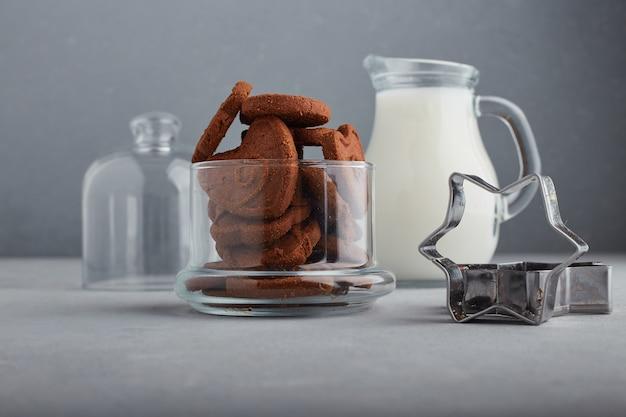 Chocoladekoekjes en een kruik melk op blauwe achtergrond.