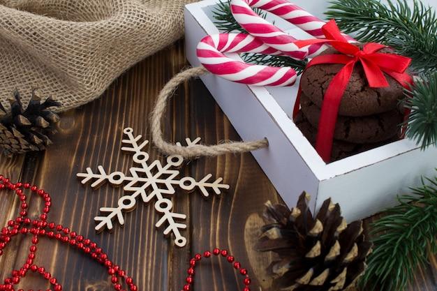 Chocoladekoekjes en kerstmissamenstelling in de witte doos op de houten oppervlakte