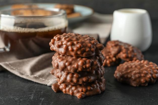 Chocoladekoekjes en kop van koffie op zwarte lijst tegen donkere achtergrond