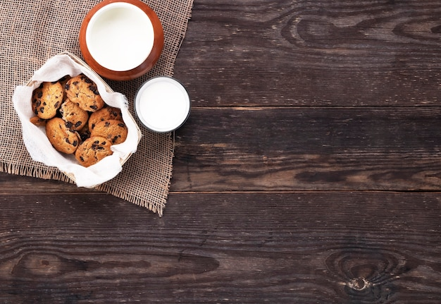 Chocoladekoekjes en melk in glas en pot op jute op een houten lijst. plat leggen.