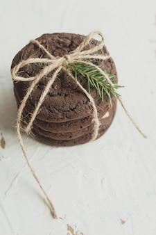 Chocoladekoekjes gebonden met een kant en versierd met een kerstboomtak