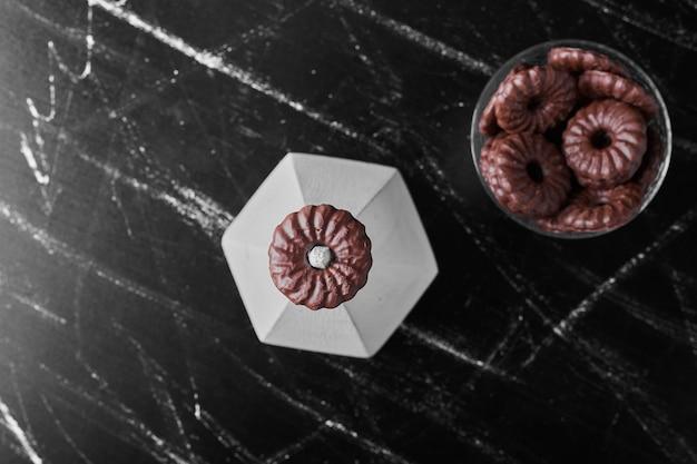 Chocoladekoekjes in een glazen beker, bovenaanzicht.