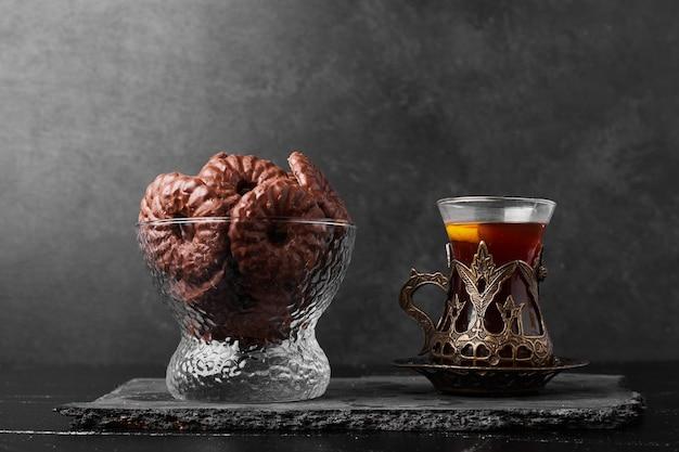 Chocoladekoekjes in een glazen beker met een glas thee.