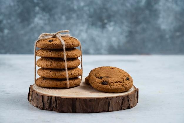 Chocoladekoekjes in touw op een houten bord.