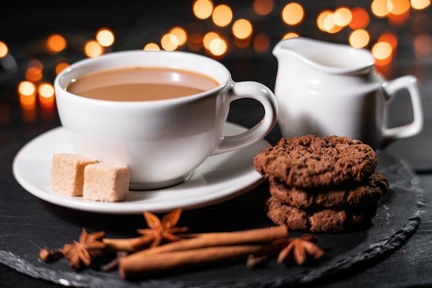 Chocoladekoekjes, koffie, kruiden op vage kerstmislichten.