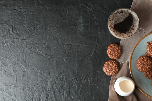 Chocoladekoekjes, kopje koffie en melk op zwarte tafel,