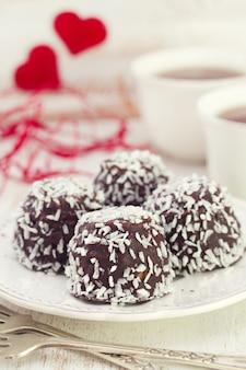 Chocoladekoekjes met kokosnoot op witte plaat en koffie op witte houten lijst