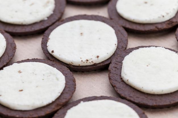 Chocoladekoekjes met romige slagroomvulling, verdeeld in stukjes biscuit en slagroomvulling
