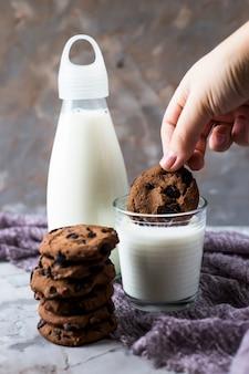 Chocoladekoekjes naast een glazen fles en een glas melk op een grijze tafel