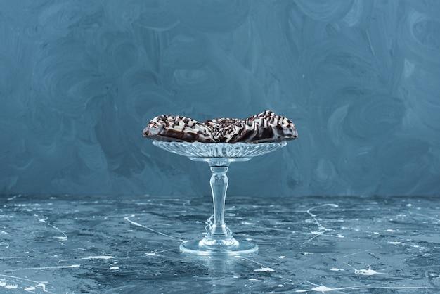Chocoladekoekjes op een glazen voetstuk, op de blauwe tafel.