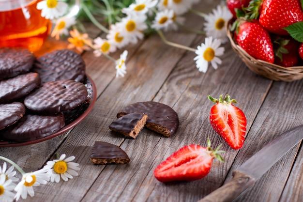 Chocoladekoekjes op een houten tafel met aardbeien, mes, kamille en een kopje thee. lekker frame