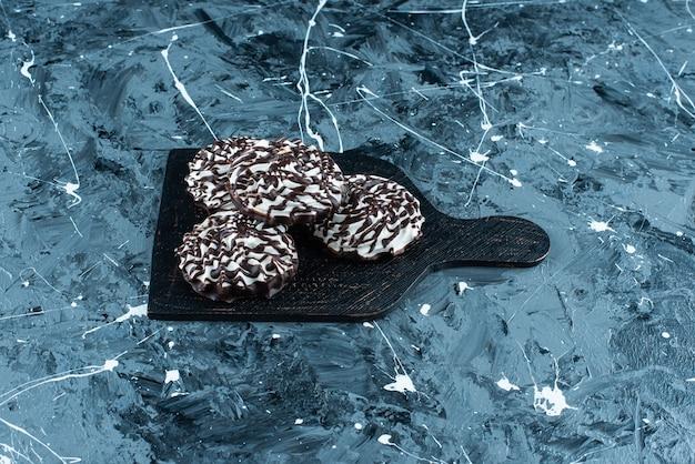 Chocoladekoekjes op een snijplank, op de blauwe tafel.