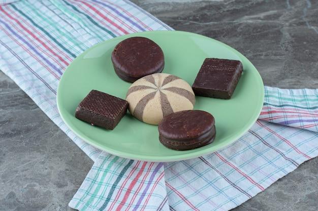 Chocoladekoekjes op groene plaat over grijs.