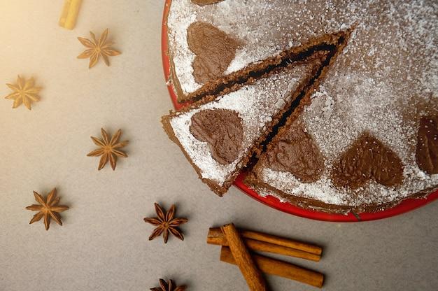 Chocoladekoekjescake met cacaoroom met kleine hartjes van poedersuiker. toetje. valentijnsdag concept. plat lag bovenaanzicht