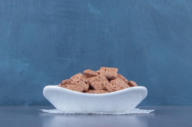 Chocolademaïs pads in kom op een onderzetter, op de blauwe tafel.