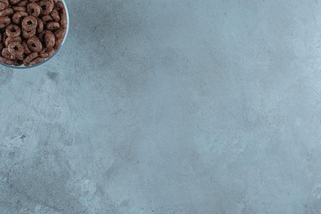Chocolademaïsring in een glazen voetstuk, op de blauwe achtergrond.