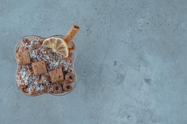 Chocolademilkshake in een glas, op de blauwe achtergrond.